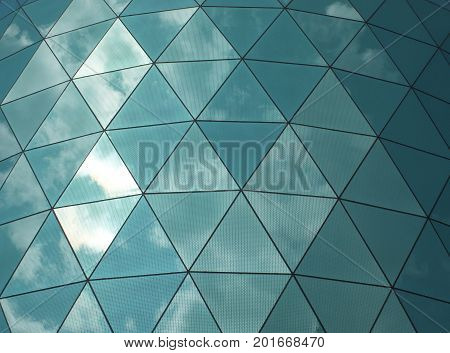 angular glass mirror cladding on a modern structure with reflected sky and clouds