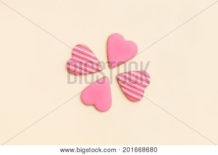 Top view on four little pink gingerbread cookies in shape of hearts on light yellow background. Flay layout. Love Valentines's day concept