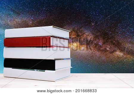 stack book on desk no labels blank spine with blurred image of milky way galaxy background long exposure photograph education back to school and science concept copy sace