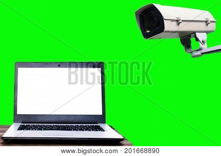 CCTV security camera system operating with blank screen laptop computer on desk for monitoring monitor video system on green background for photo montage surveillance security technology concept