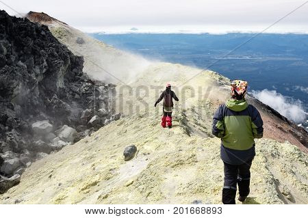 Mountain hiking on Kamchatka Peninsula: two young women tourists walking along sulfur fumarole field in summit crater of active Avacha Volcano on Kamchatka. Eurasia Russian Far East Kamchatka Region