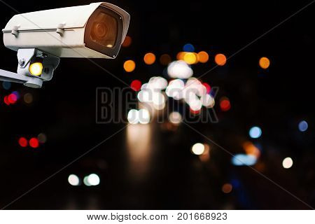 CCTV security outdoor camera system operating with abstract night light bokeh blurred view of street traffic light in the city at night surveillance security technology concept