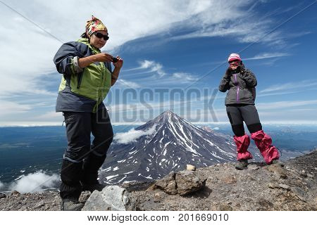 AVACHA VOLCANO KAMCHATKA PENINSULA RUSSIA - AUG 7 2014: Mountain hiking - two young women tourists stand of top of summit crater of active Avachinsky Volcano on background of cone of Koryak Volcano