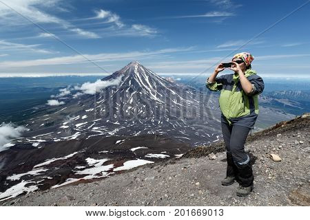 AVACHA VOLCANO KAMCHATKA PENINSULA RUSSIAN FAR EAST - AUG 7 2014: Women tourists standing on edge of crater of active Avacha Volcano and photographed on smartphone on background of Koryak Volcano.