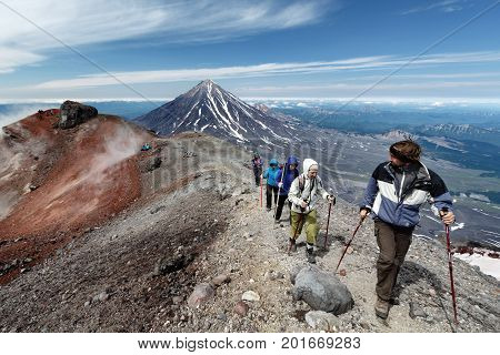 AVACHA VOLCANO KAMCHATKA PENINSULA RUSSIAN FAR EAST - AUG 7 2014: Group of hikers climbing along the edge of summit crater of active Avachinsky Volcano on background of cone of Koryak Volcano.