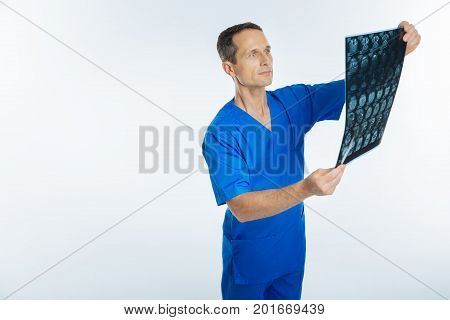 Attentive examination. Cropped shot of a male practitioner holding an x ray scan picture and examining it confidently alone.