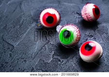 Funny halloween treat - jelly eyeballs on dark background. Copy space