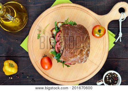 Big sandwich with pieces of meat arugula tomato cereal ciabatta on a cutting board on a dark wooden background. Top view.