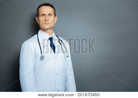 Always here to help. Waist up shot of an experienced practitioner wearing a white coat standing over the grey background and looking into the camera confidently.