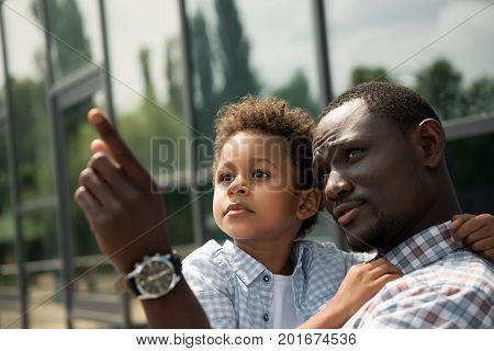 african american father and son looking away and pointing with finger while standing outside