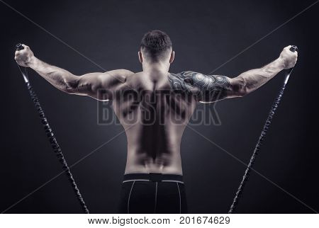 Sports concept. Athletic young man exercising with rubber band against a dark background
