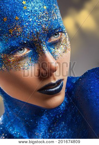 Close-up of a young woman with make-up made of blue sequins with stars. Art fashion