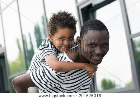 happy african american father piggybacking son and smiling at camera