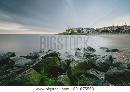 Lighthouse and village of the former Island of Urk alongside the lake IJsselmeer long exposure with smooth water and dynamic sunset in the Netherlands