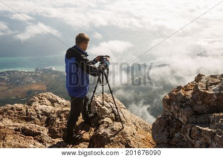 Man standing with a tripod and camera on a high mountain peak above clouds and sea. Photographer adjusting dslr settings on rocky summit. Ai Petri, Yalta, Crimea.