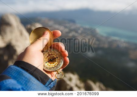 Point of view photo of explorer man searching direction with golden compass in his hand above clouds with autumn mountains and sea background. Navigation and travel concept