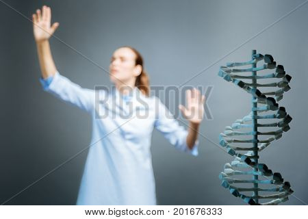 Innovative study. Selective focus on a 3d dna model standing in a lower right angle with a female scientist pretending to touch an invisible screen with two hands.