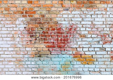 The texture of the brick wall in some places chaotically painted with old paint of blue red yellow and white. You can use it as a background for your design.