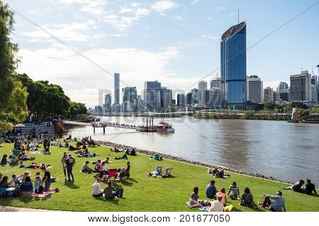 Brisbane Australia - July 9 2017: people sitting on the Brisbane River South Bank watching the Brisbane city skyline.