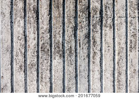 The texture of unpainted striped old concrete fence. You can use it as a background for your design.