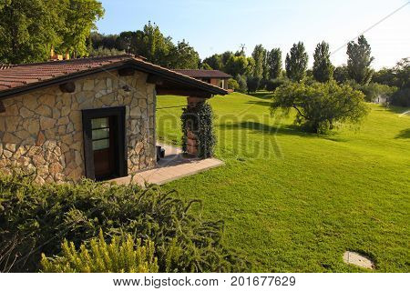 Small villa with garden and green grass in summer village resort Italy