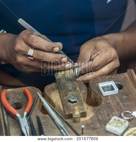 Jeweler making handmade jewelry on vintage workbench. Craft of jewelery making. Repairing ring by inlaid tight gem.