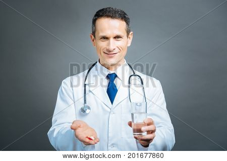Support is what really matters. Waist up shot of a friendly looking male practitioner smiling into the camera while bringing a handful of pill and a glass of water.