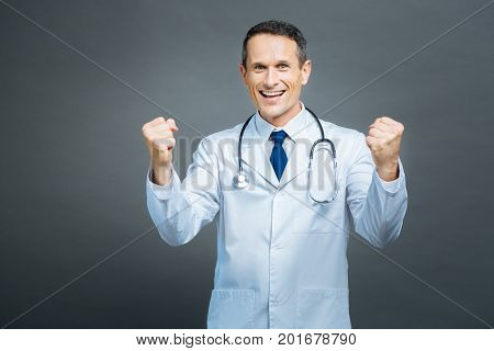 Hurray. Waist up shot of an excited male doctor grinning broadly while looking into the camera and gesturing over the background.
