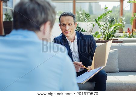 Closing a deal. Pleasant smart handsome businessman holding a folder with documents and looking at his business partner while closing a deal with him