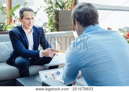 Professional negotiations. Successful nice handsome entrepreneurs sitting opposite each other and talking while having business negotiations