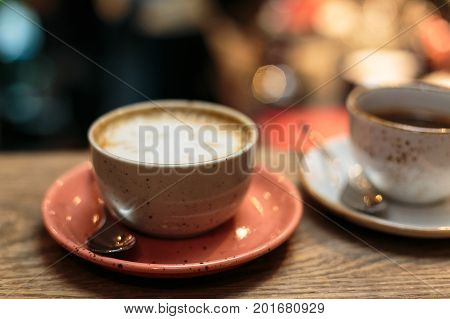 Cup of Cappuccino Coffee with foam froth cover on top. Cafe shop bokeh background.