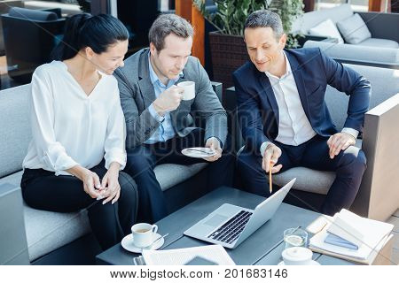 We are interested. Nice smart pleasant entrepreneurs sitting on the sofa and looking at the laptop screen while being interested in the project