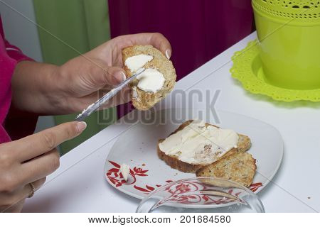 The Woman Is Spreading Butter On Toast For Herself For Breakfast.