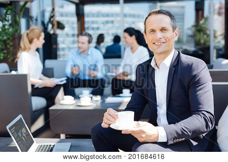 Ambitious person. Joyful delighted optimistic man smiling and dreaming about his success while holding a cup of coffee