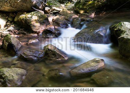 Cascade falls over mossy rocks. Forest cascade