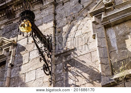 Old lamp on a wall of the cathedral of Santiago de Compostela Spain