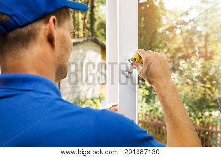 worker installing plastic white pvc window handle