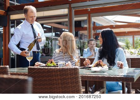 At the restaurant. Pleasant cheerful friendly waiter holding a bottle of wine and serving customers while doing his job