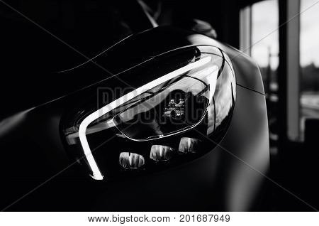 Minsk Belarus - August 26 2017: Headlight close-up of Mercedes Benz AMG GT 50 Edition sports car. A new 2017 supercar designed to celebrate the 50th anniversary of the AMG company