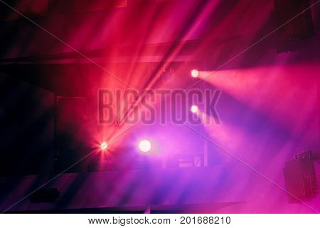 Lighting equipment on the stage of the theatre during the performance. The light rays from the spotlight through the smoke. Red and purple beams of light.