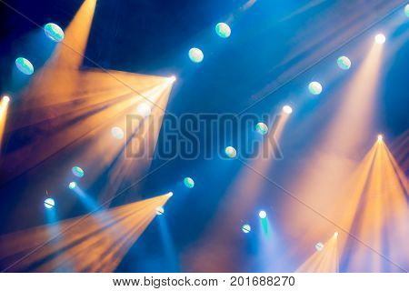 Lighting equipment on the stage of the theatre during the performance. The light rays from the spotlight through the smoke. Blue and yellow rays of light.