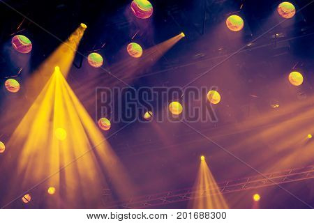 Lighting equipment on the stage of the theatre during the performance. The light rays from the spotlight through the smoke. Yellow rays of light.