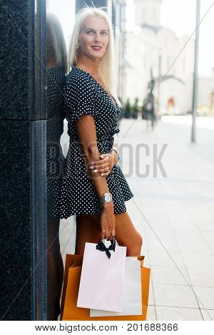 Full-length photo of young blonde in dress with purchases on city street near buildings