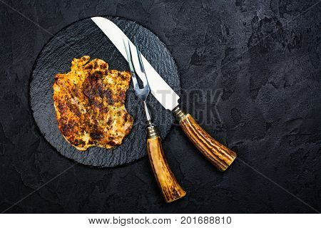 Chicken steak, fork and knife on slate board. Dark stone background. Copy space