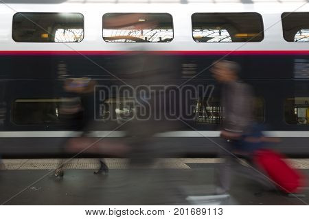 Subway train at the station. People coming to or leaving train station platform. Motion blur. City life.