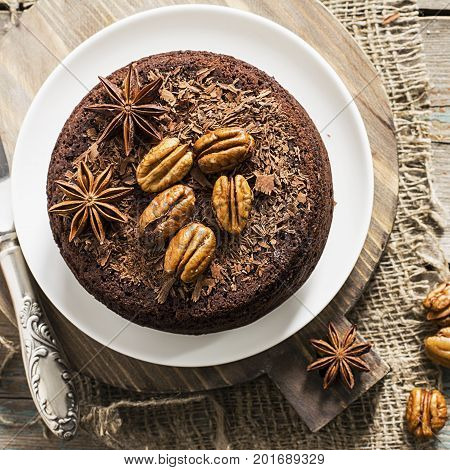 Chocolate crazy pie for a cozy autumn tea with pecans and spices on a simple wooden background. Top view. Natural light