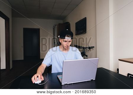 The student is carefully looking into the monitor of his laptop while sitting at the table in his home room
