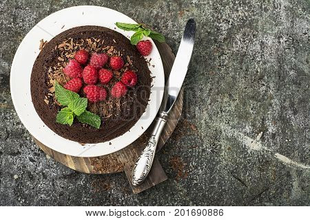 Chocolate crazy pie with juicy raspberries on a simple gray background with chocolate chips decorated with mint. Top View