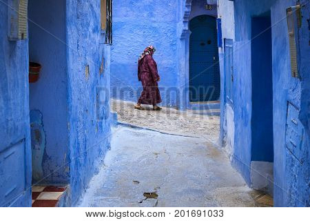 Chefchaouen Morocco - April 10 2016: Moroccan woman walking in a narrow street in the town of Chefchaouen in Morocco North Africa