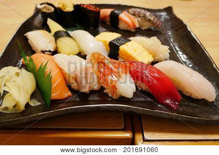 Close up of sashimi sushi set on black plate in Otaru japanese restaurant delicious gourmet menu.